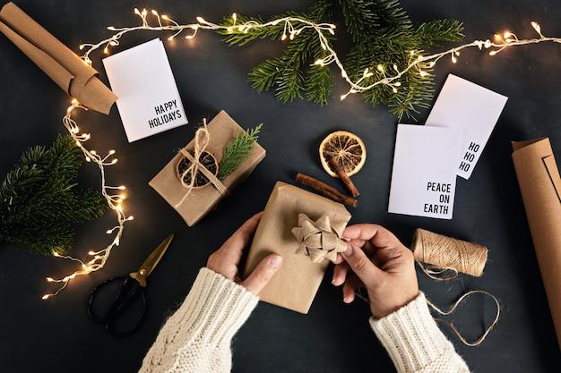 リサイクルクラフト紙で環境にやさしい代替の緑のクリスマスプレゼントを包む女性の手