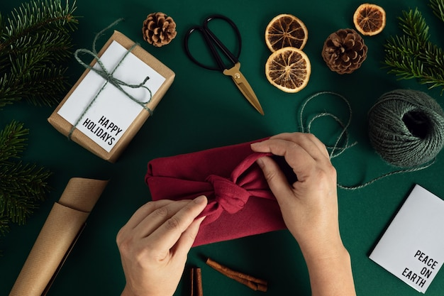 Женщина руки, упаковывающие подарок фуросики