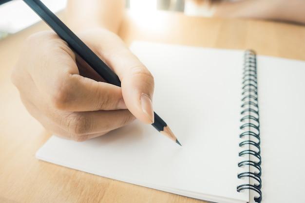 Женщина руки, писать на книгу в офисе. деловая женщина, работающих на стол из дерева. деловая женщина, работающая с ноутбуком и канцелярские принадлежности на вид сверху. копирование пространства. винтажные картины стиля эффекта.