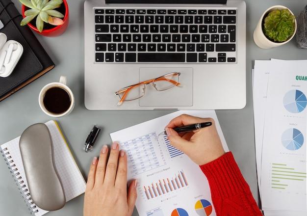 灰色のオフィスのデスクトップビューのラップトップの近くでレポートに書く女性