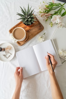 Woman hands writing in an opened blank notebook with coffee, a plant and flowers on a wooden tray