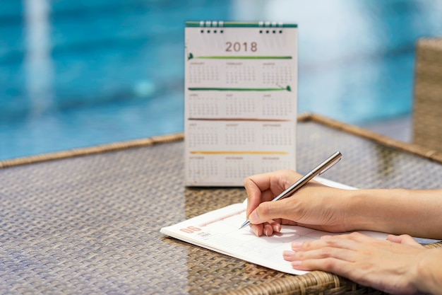 Woman hands writing plan on notebook, planning agenda and schedule using calendar