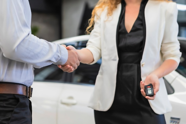Woman handshake vehicle saleswoman with customer presenting new cars at showroom.