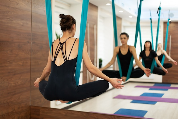 Woman hang in hammock in lotus position fly yoga stretching exercises in gym