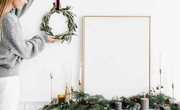 空白の白いフレームの横にクリスマスリースをぶら下げている女性