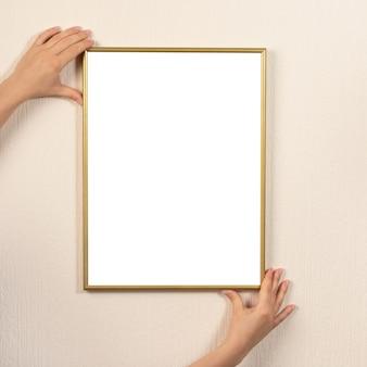 壁にフレームをぶら下げている女性。女性の手は明るい壁に金のフレームを保持します