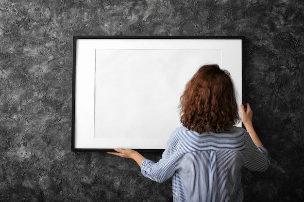 Woman hanging blank photo frame on dark wall