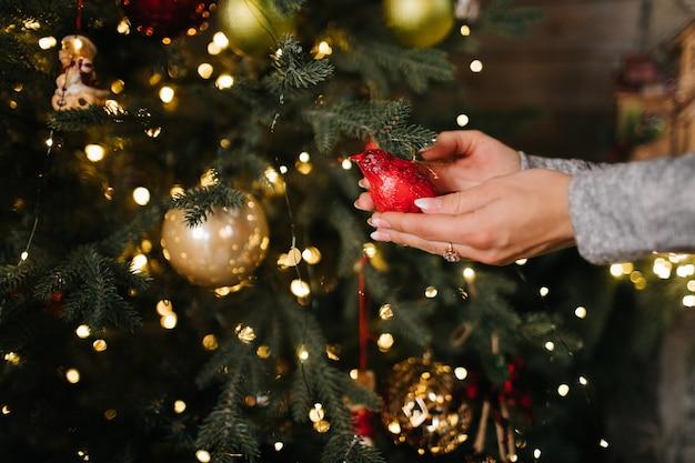 ボケライトとツリーにクリスマスボールをぶら下げの女性