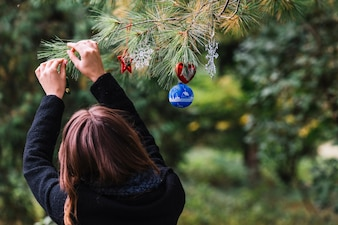 Woman hanging Christmas toys on twig in forest