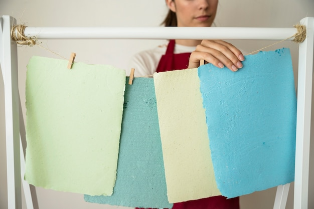 Woman hanging colorful handmade papers on string