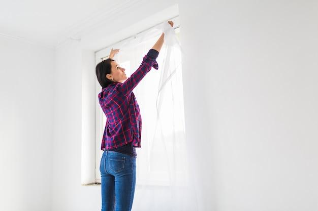 Женщина висит занавески на окне