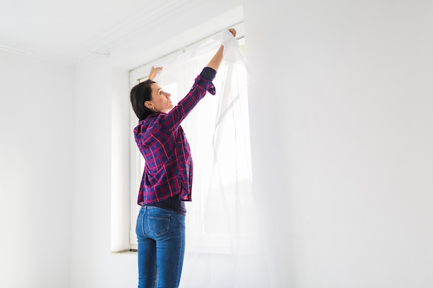 Woman hanging curtains on window