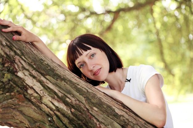 木の近くにぶら下がっている女性