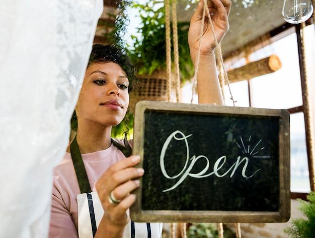 Женщина висит открытый знак окна стекла