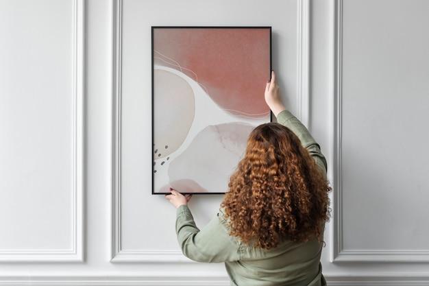 디자인 공간이 있는 벽에 액자를 걸고 있는 여성