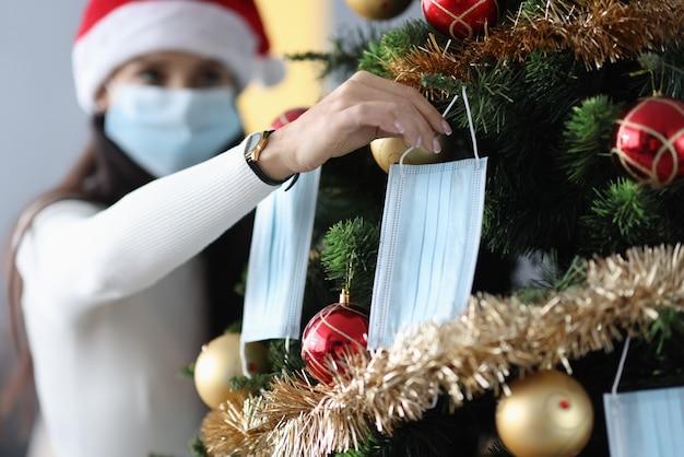 クリスマスツリーに保護医療マスクをぶら下げている女性