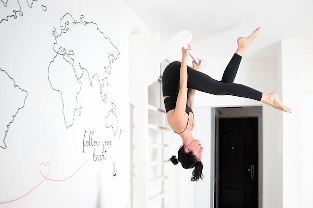 Женщина висит вверх ногами при растяжении
