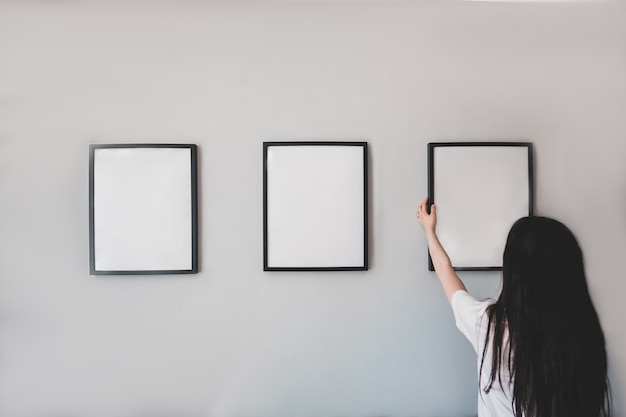 Woman hangs a frame on the wall. empty place for your photo, picture, design or logo.