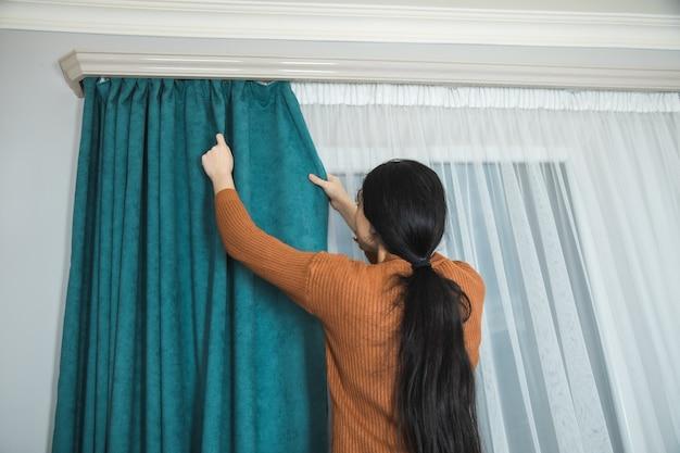 Женщина вешает занавеску в модной комнате