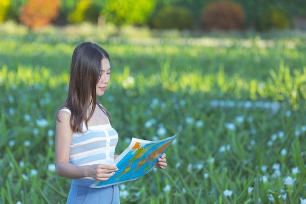 Donna felicemente tenendo una mappa turistica nel giardino fiorito