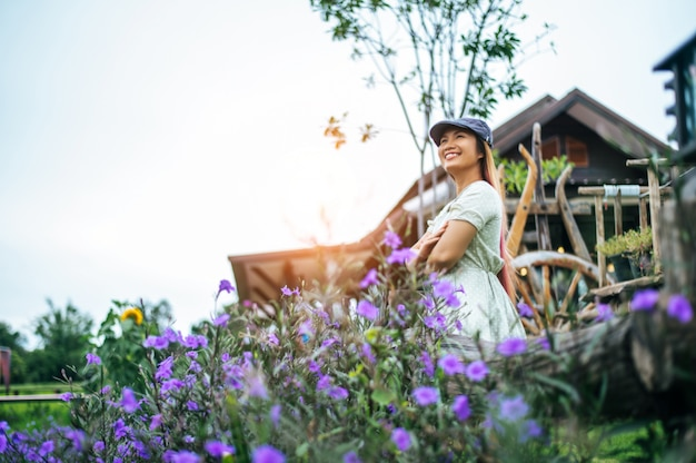 Woman happily stand in the flower garden in the wooden railings