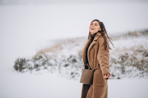 Woman happy in coat in winter outside in park