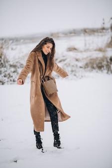 Женщина счастлива в пальто зимой в парке
