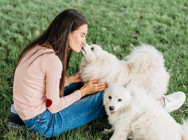 Женщина счастлива играть с милыми собаками