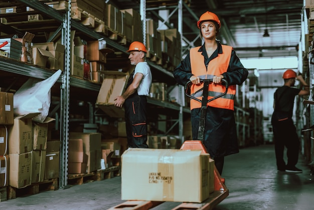 Woman in hardhat using forklift cart in warehouse