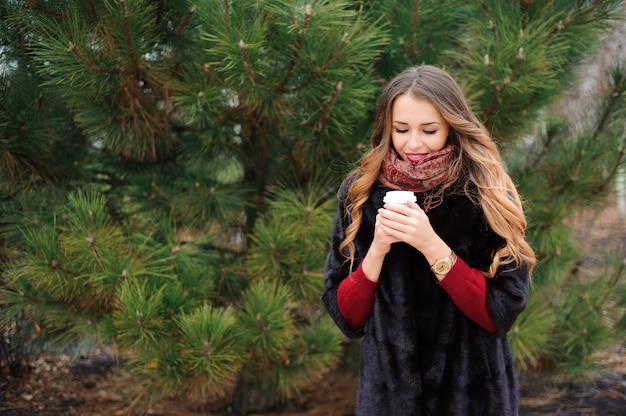 女性は秋の日に路上でコーヒーブレークを持っています