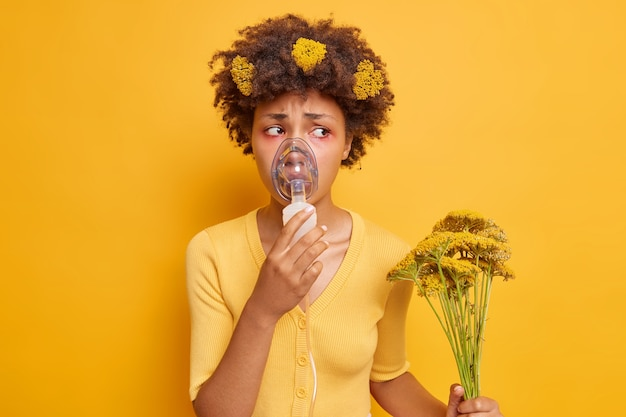 La donna ha problemi di attacco asmatico con la salute indossa una maschera per l'ossigeno che aiuta a respirare trattiene i fiori di campo che causano una reazione allergica ha occhi gonfi rossi isolati sul muro giallo
