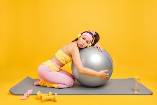 Женщина делает тренировку по коррекции фигуры, опирается на фитбол, одетая в спортивную одежду, слушает музыку в наушниках, позирует на коврике для фитнеса
