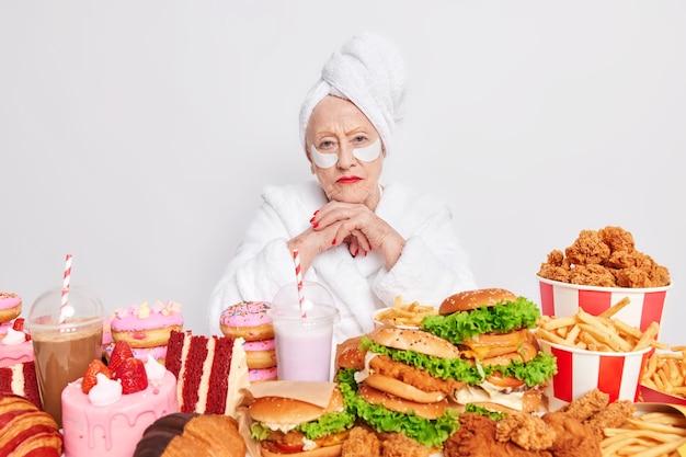 Женщина проводит день читмила дома, держит руки под подбородком, позволяет есть вкусные бургеры, пончики и пирожные, накладывает косметические патчи под глаза