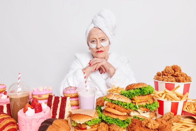 Woman has cheat meal day at home keeps hands under chin affords eating tasty burgers doughnuts and cakes applies beauty patches under eyes