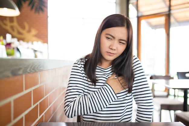 У женщины болит грудь в кафе