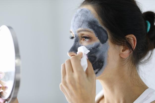 У женщины на лице глиняная косметическая маска. концепция омоложения и очищения кожи лица