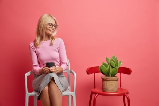 女性はコーヒー ブレークを持っており、飲み物のマグカップを保持し、ピンク色に隔離された椅子に座っている鉢植えのサボテンを注意深く見る