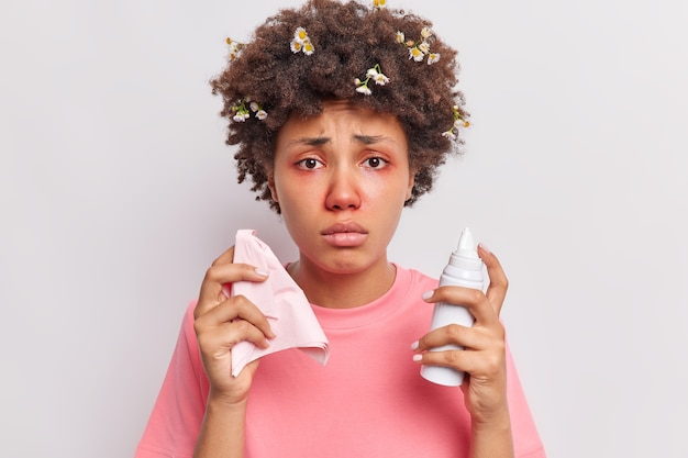 Woman has curly hair with stuck camomile flowers holds nasal spray and napkin dressed in pink t shirt suffers from stuff nose and redness