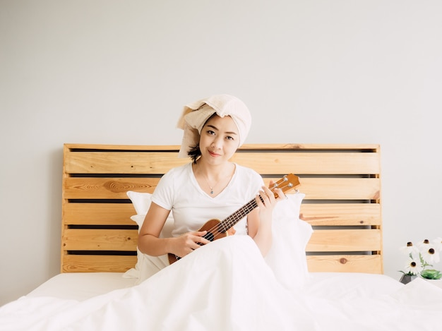 Woman has a fine relax day with her ukulele on bed.