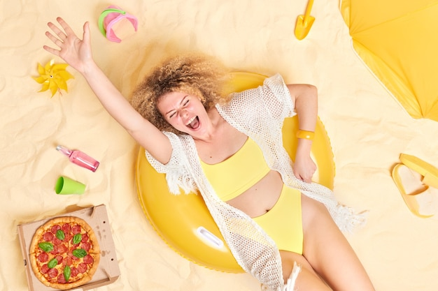 Woman has fun at beach lies on swimring dressed in yellow bikini raises arm enjoys vacation surrouunded by beach accessories poses on white sand.