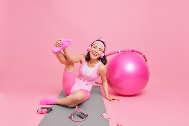 La donna si diverte sul tappetino per il fitness alza e allunga le gambe si allena a casa ascolta musica tramite le cuffie usa l'attrezzatura sportiva vestita con abbigliamento attivo isolato sul rosa