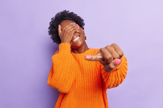 여자는 즐겁게 웃고 있다. 카메라에 검지 손가락으로 손을 가리키며 눈을 즐겁게 하는 것은 보라색에 격리된 주황색 니트 스웨터를 입는 재미있는 것을 본다