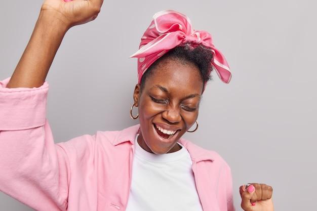 女性はパーティーで楽しんでいます腕を上げて音楽に合わせて踊ります灰色のスタジオで隔離されたファッショナブルな衣装に身を包んだイベントの楽しい瞬間を楽しんでいます