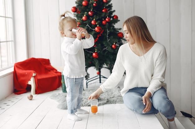 La donna si diverte a prepararsi per il natale. madre in maglione bianco che gioca con la figlia. la famiglia sta riposando in una stanza festiva.