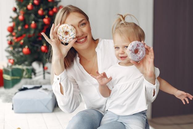 여자는 크리스마스를 준비하는 재미 있습니다. 흰색 셔츠에 어머니는 그녀의 딸과 함께 재생됩니다. 가족은 축제 방에서 쉬고 있습니다.