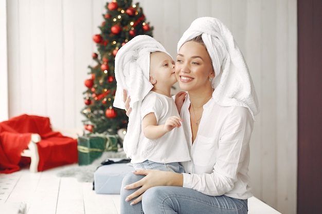 Женщина весело готовится к рождеству. мать в белой рубашке играет с дочерью. семья отдыхает в праздничном зале.