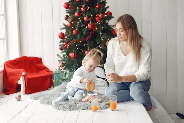 Женщина весело готовится к рождеству. мать в белом свитере, играя с дочерью. семья отдыхает в праздничном зале.