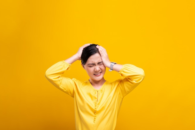 Woman has headache isolated over yellow wall