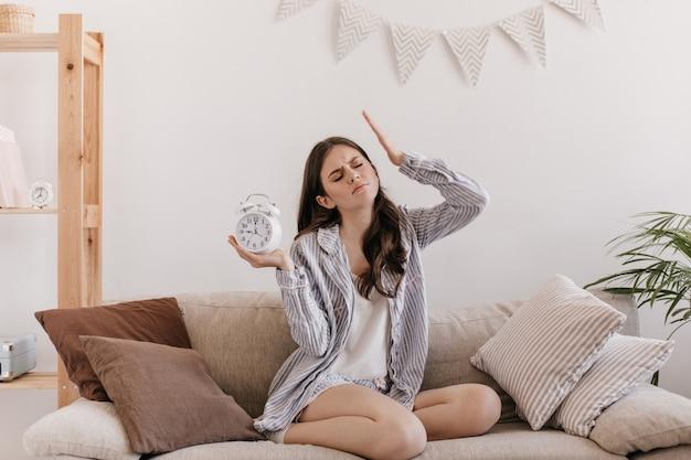 女性は頭痛がします。目覚まし時計とリビングルームでポーズをとるパジャマの女性