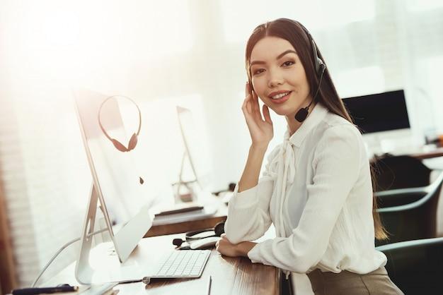 女性は彼女が顧客に話すヘッドホンを持っています。